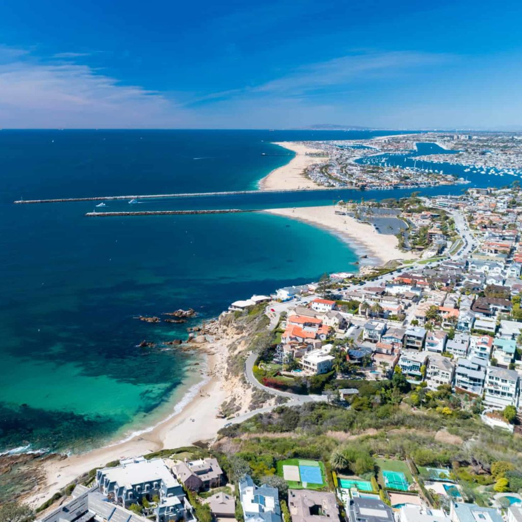 Aerial view of coastal Newport Beach in Orange County, California, USA with coast, sand and blue skies.